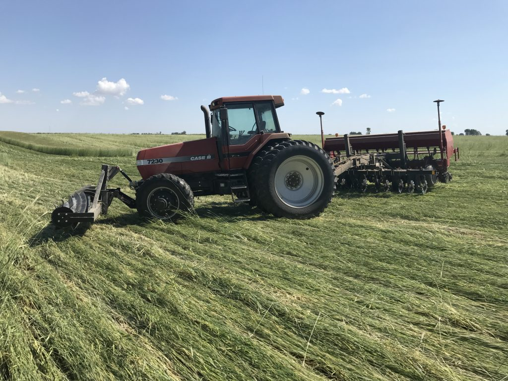 Case Magnum 7230 tractor with front mounted roller crimper